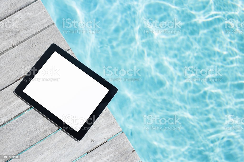 Tablet with empty screen on the wooden pool deck stock photo