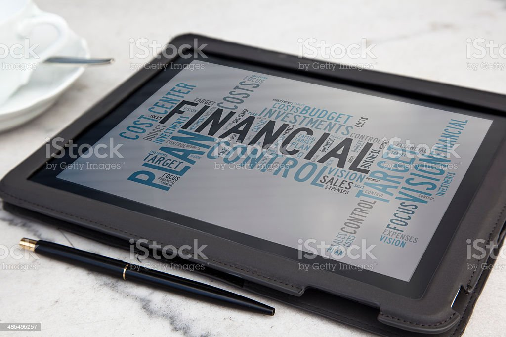 tablet with financial word cloud stock photo