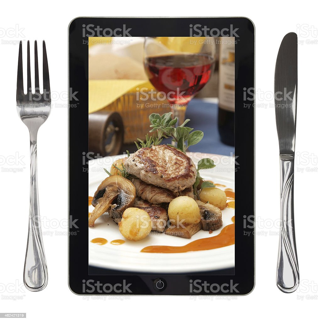 Tablet with food photo, fork and knife, conceptual royalty-free stock photo
