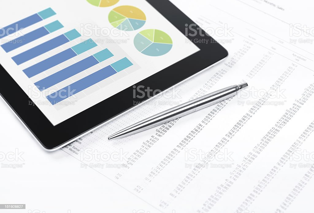 Tablet with graphs, charts next to pen royalty-free stock photo