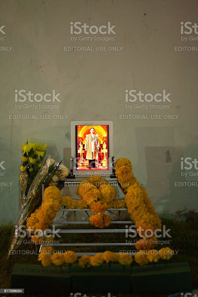 Tablet with iamge of King Bhumipol and flowers around stock photo