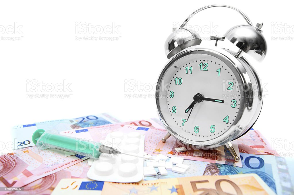 Tablets, a syringe and an alarm clock on money. royalty-free stock photo