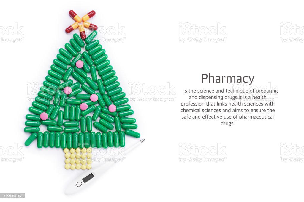 Tablets in form of Christmas tree and thermometer under it stock photo