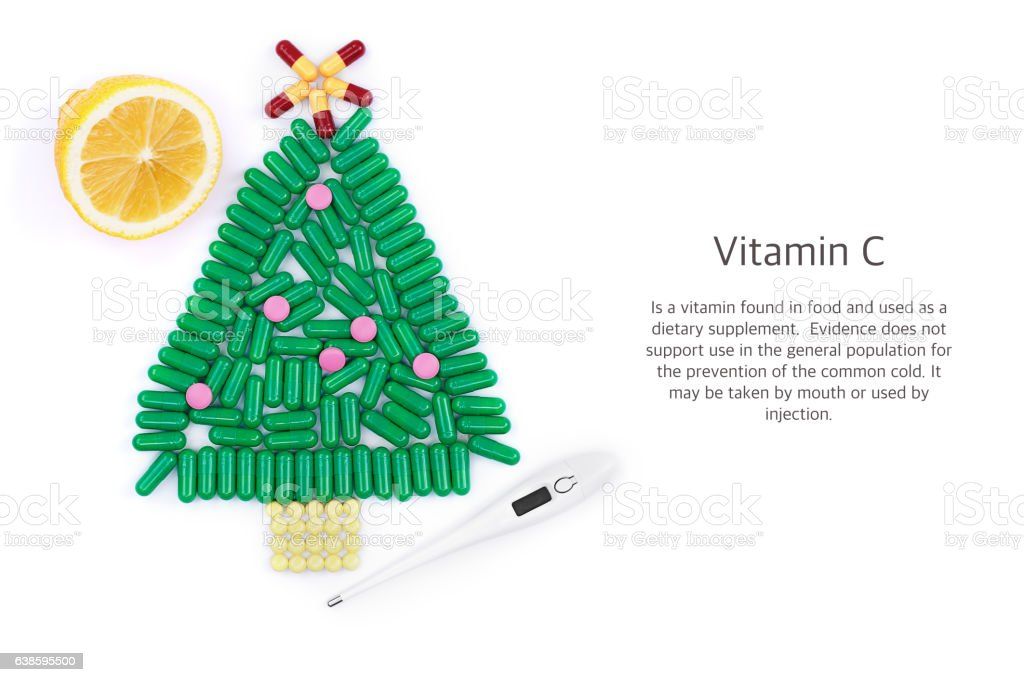 Tablets in form of Christmas tree thermometer and lemon underneath stock photo
