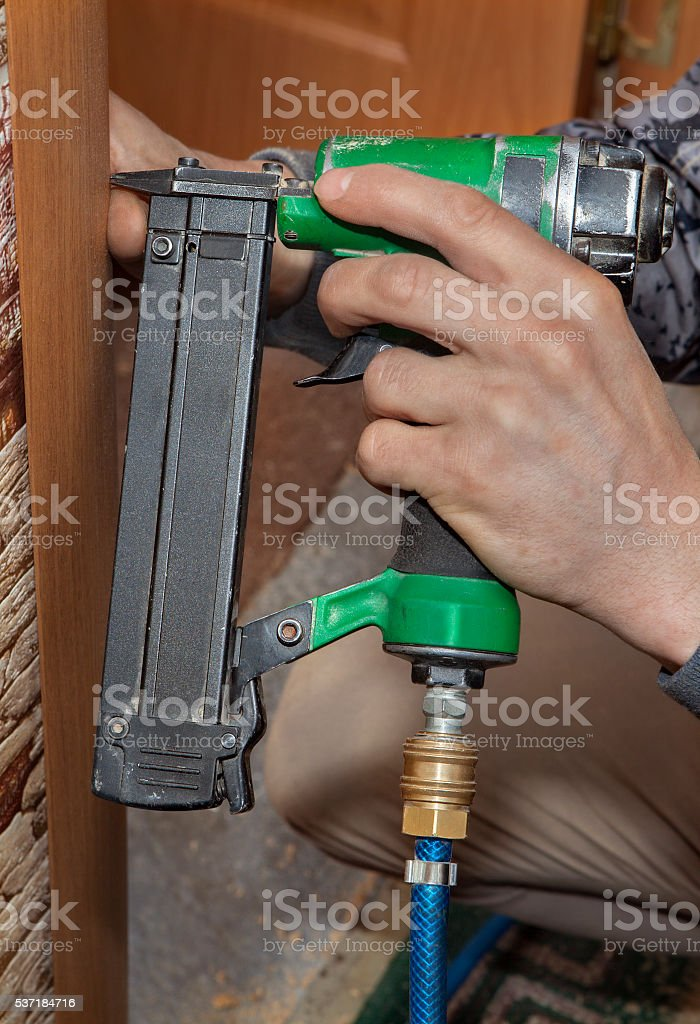 Tack head casing to  jamb, using nail gun, shoot brad. stock photo