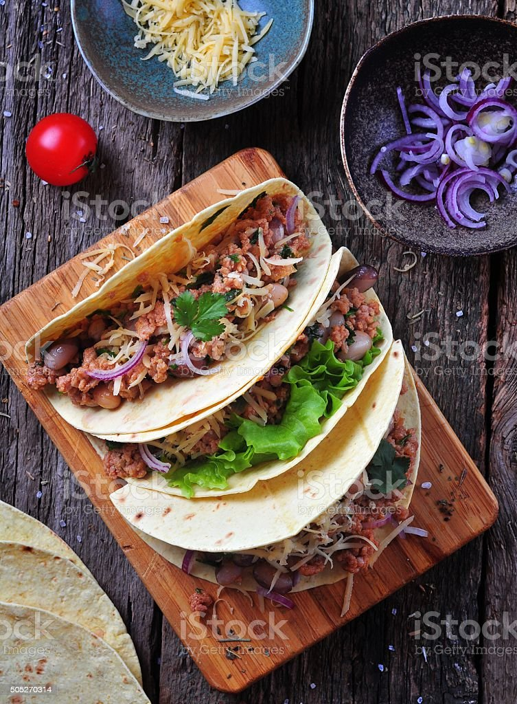 tacos with minced meat with beans, cheese and onion stock photo
