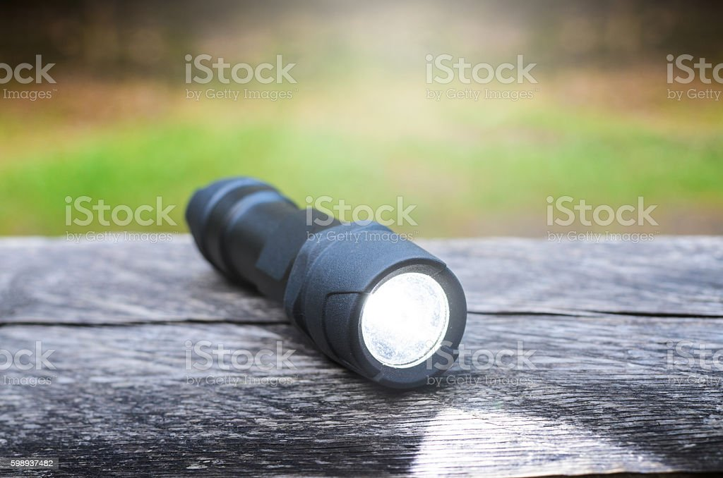 Tactical waterproof flashlight on wooden base with light beam stock photo