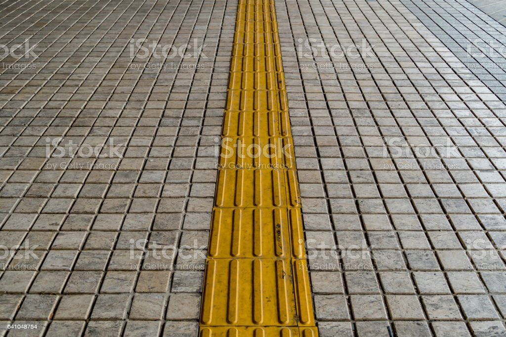 Tactile paving for blind handicap on tiles pathway stock photo
