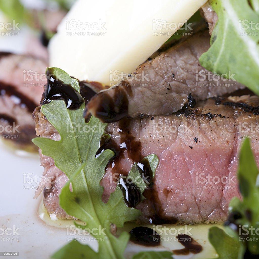 tagliata di manzo guarnita con parmigiano e rucola royalty-free stock photo