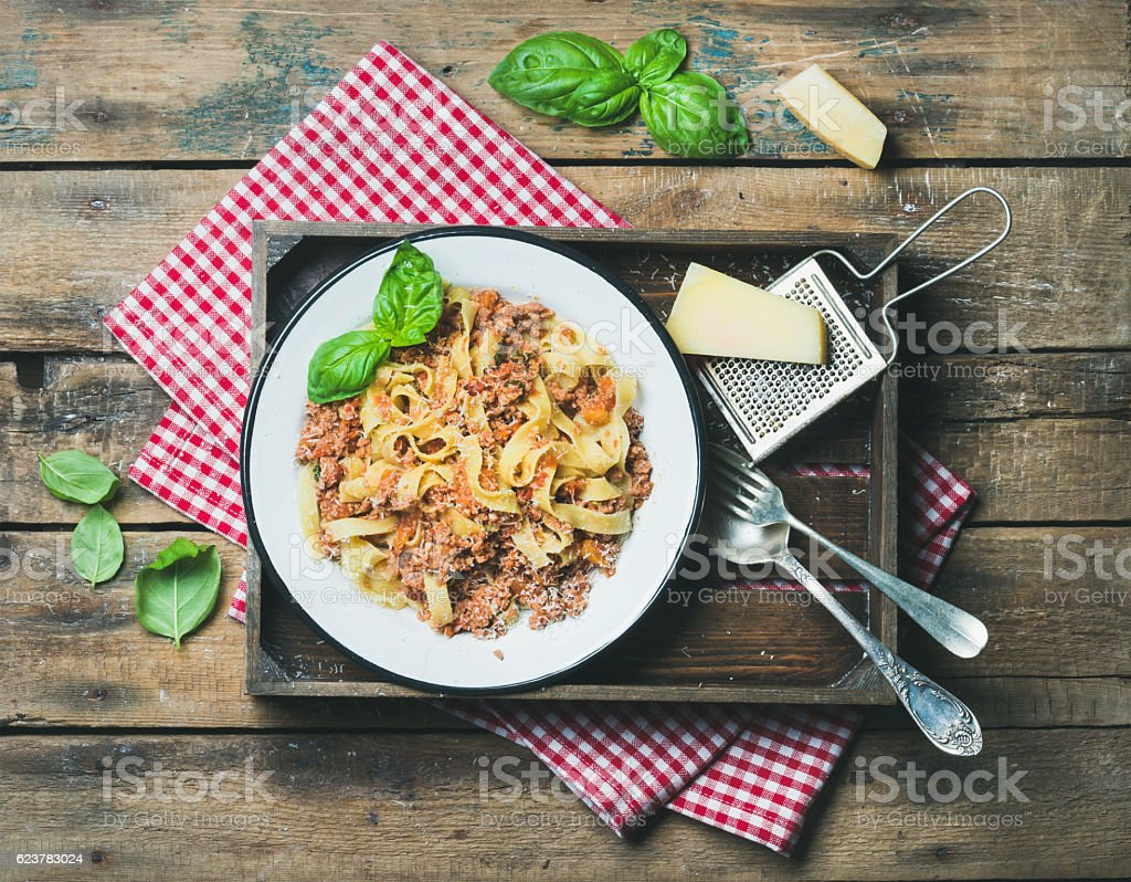 Tagliatelle Bolognese with Parmesan and basil in wooden tray stock photo