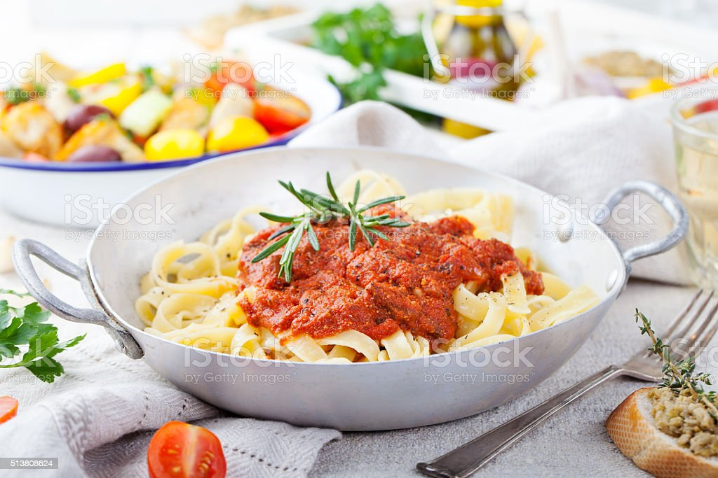 Tagliatelle pasta with tomato sauce and red pesto Italian cuisine stock photo