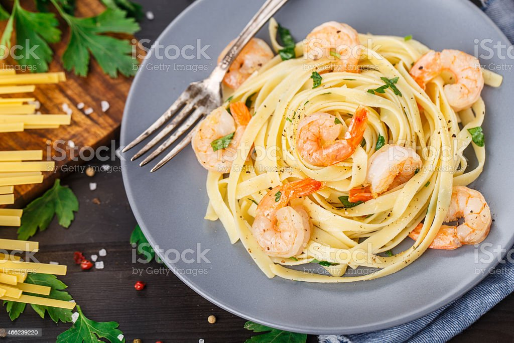 Tagliatelle with shrimps and parsley stock photo
