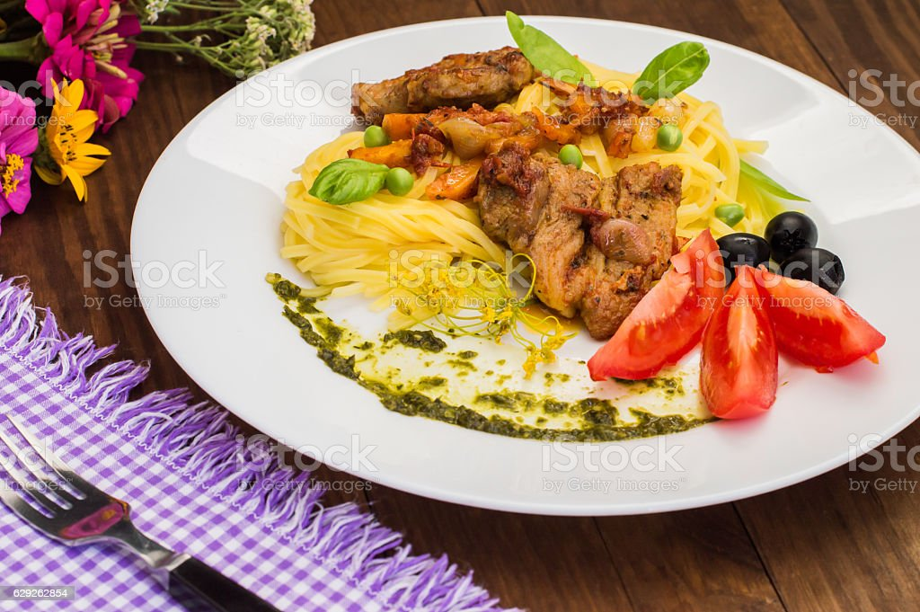 Tagliolini with meat in tomato sauce, olives and   spinach. Wooden stock photo