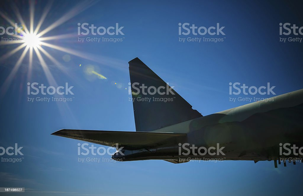 Tail end of B-52 Stratofortress mid-air in front of sunbeam. royalty-free stock photo