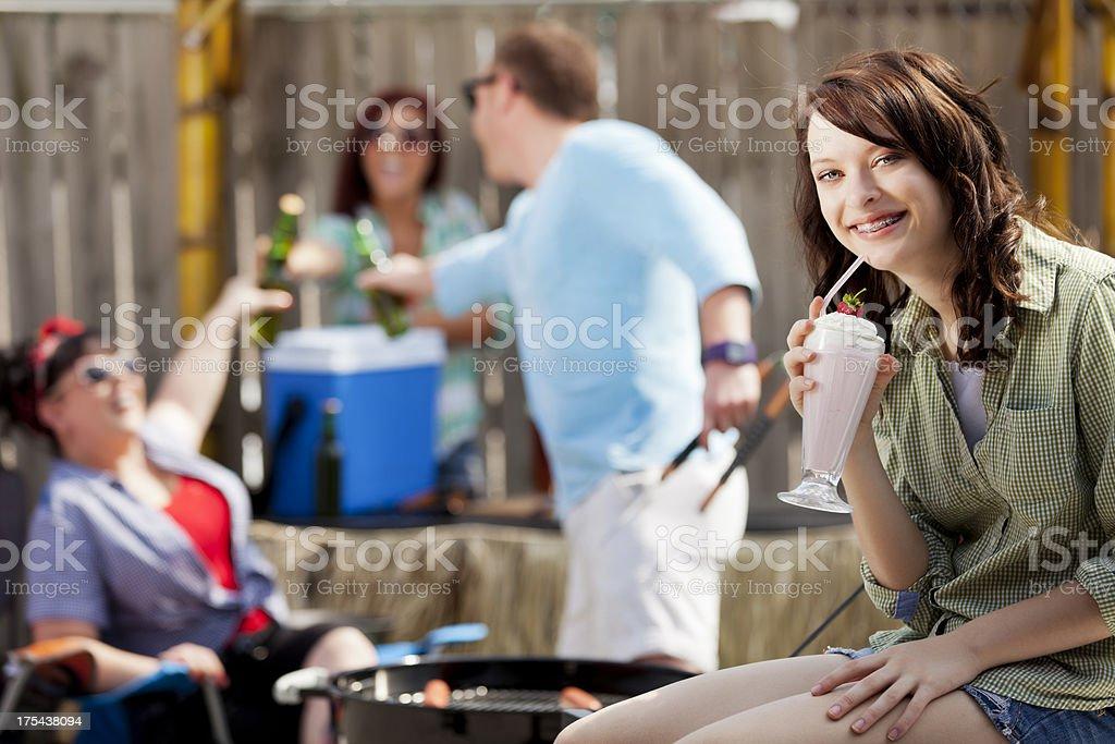 Tailgate party: teenage girl enjoying milkshake at an outdoor BBQ royalty-free stock photo