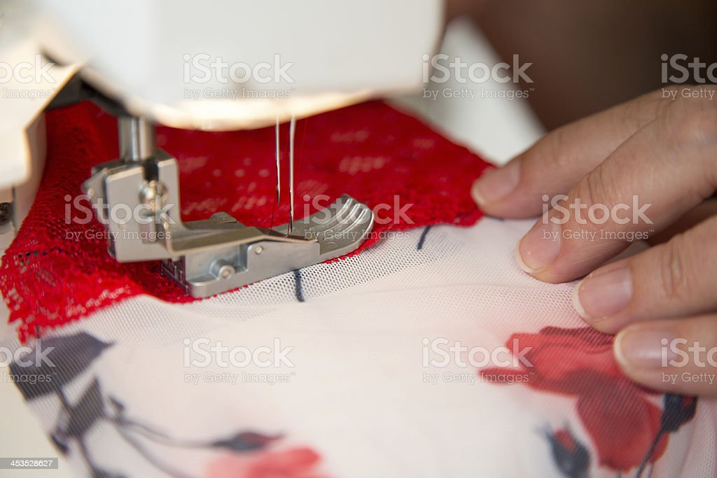 Tailor at sewing machine tailoring lingerie or a bra royalty-free stock photo
