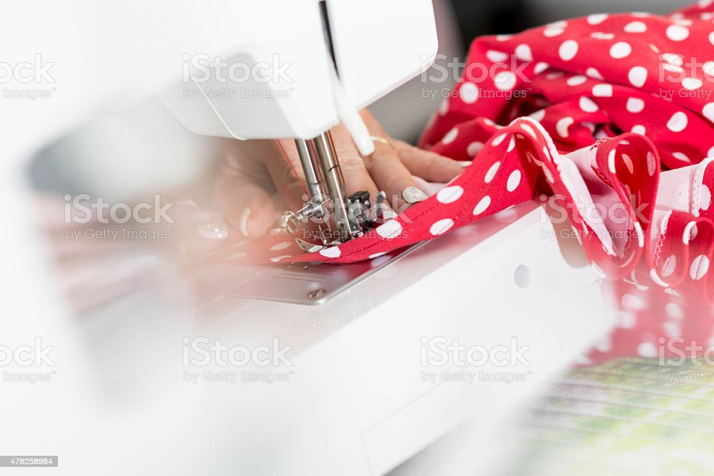 Tailor at work on sewing machine stock photo