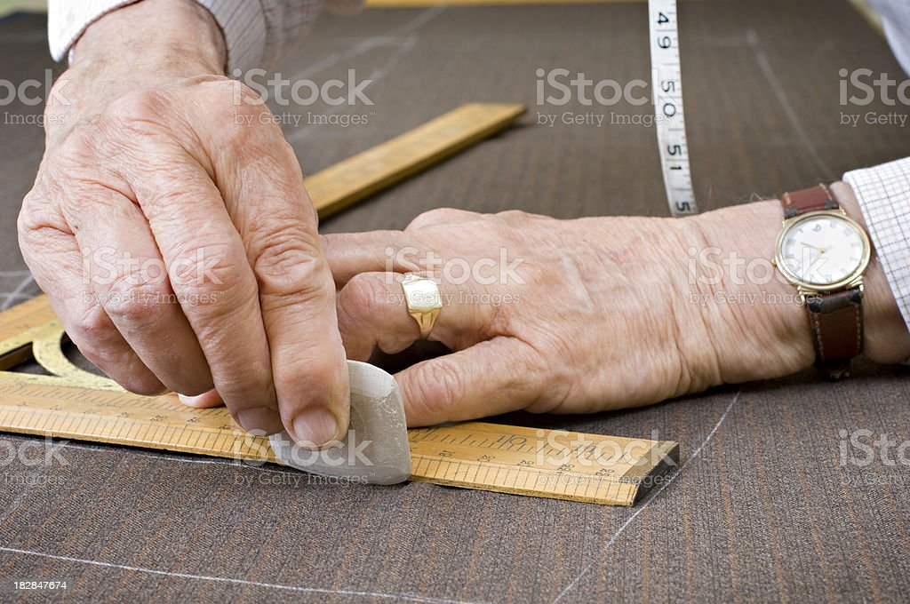 Tailor At Work With Chalk Square and Tape Measure stock photo