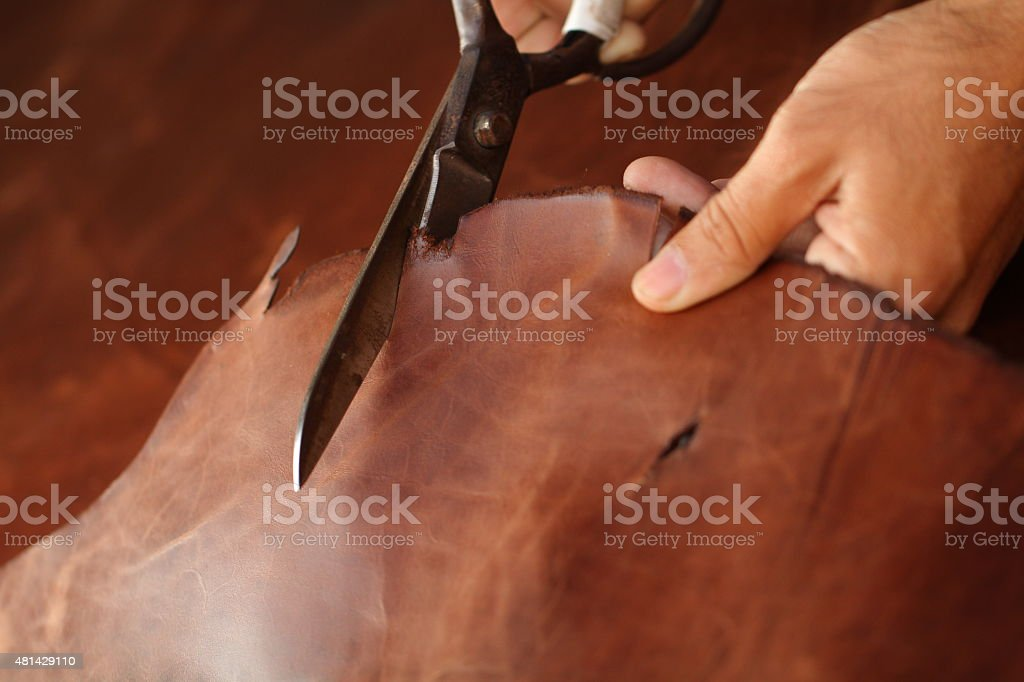 Tailor cutting animal skins at textile factory stock photo