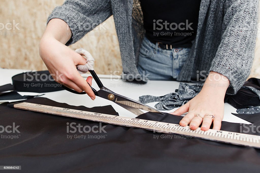 Tailor cutting out dark fabric with large scissors stock photo