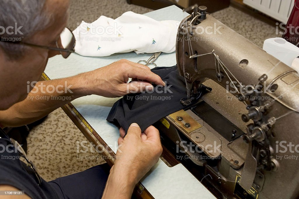 Tailor in his workshop...working with sewing machine royalty-free stock photo
