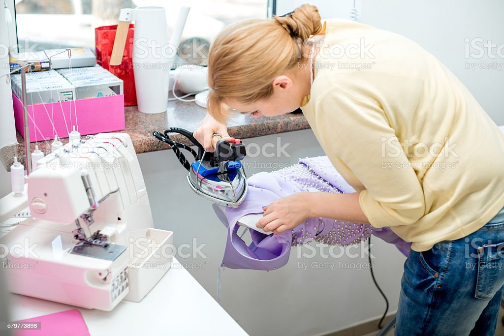 Tailor ironing the fabric. stock photo