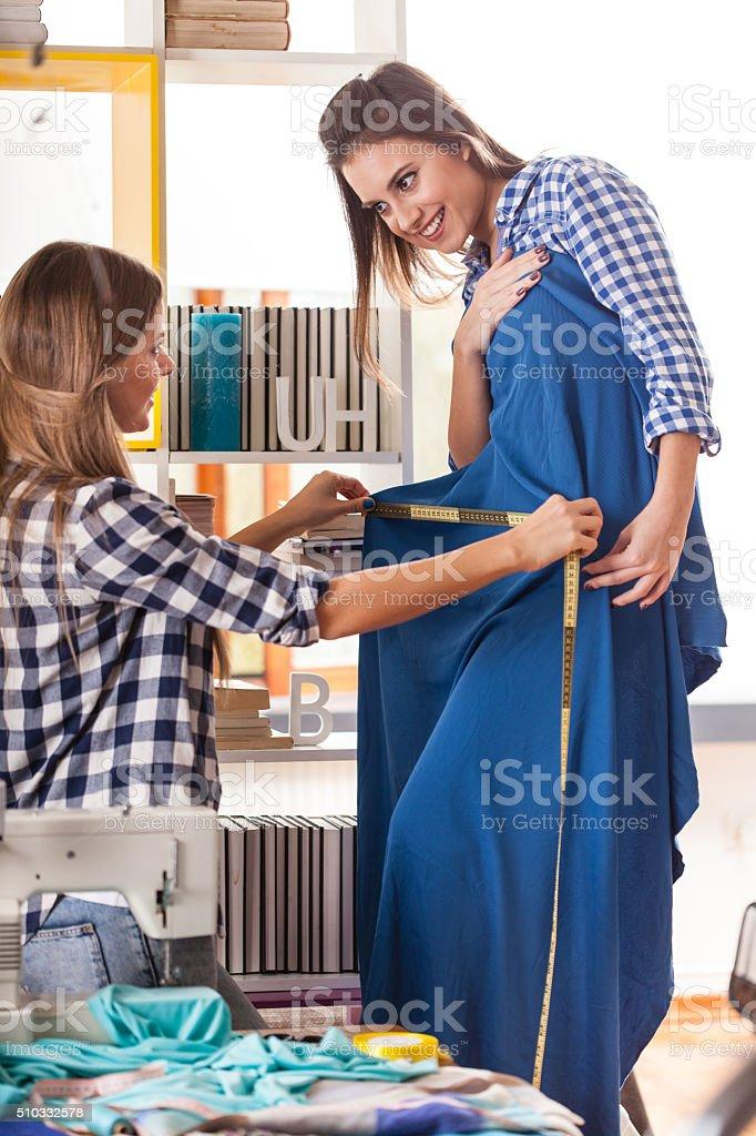 Tailor measuring customer, choosing fabric stock photo