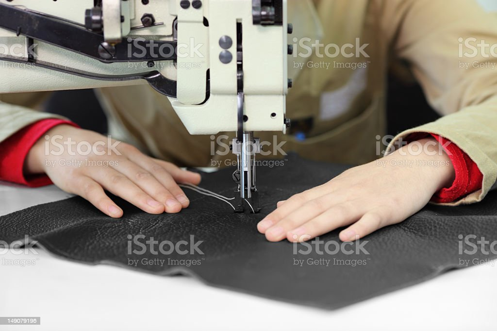 Tailor sewing a piece of black leather royalty-free stock photo