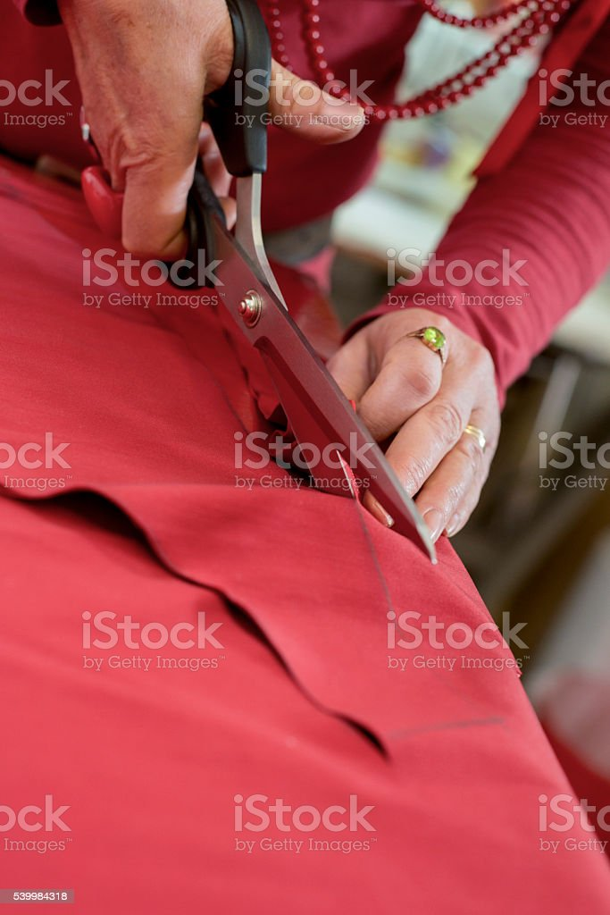 Tailor Shears Cutting Through Red Cloth stock photo