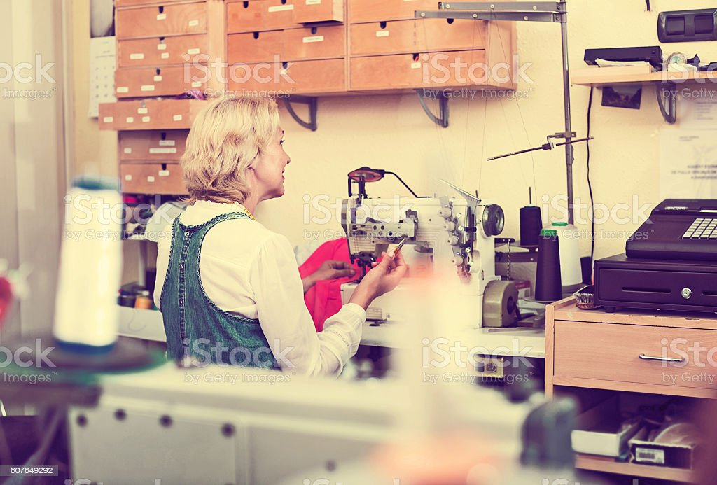 Tailor using sewing machine stock photo