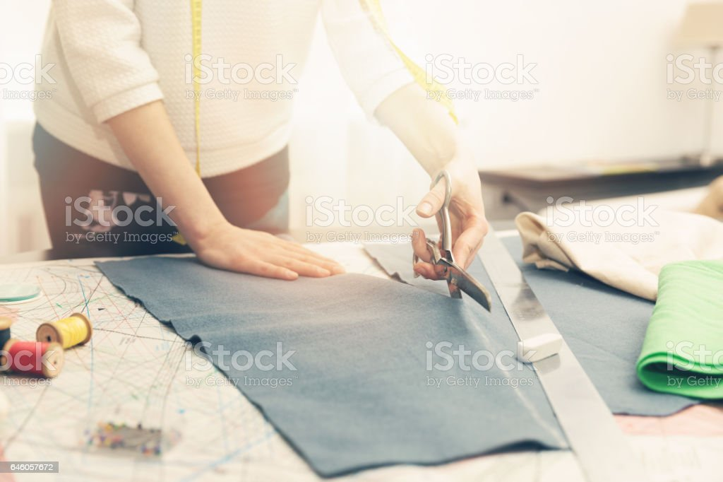 tailoring workshop - woman tailor cutting fabric with scissors stock photo