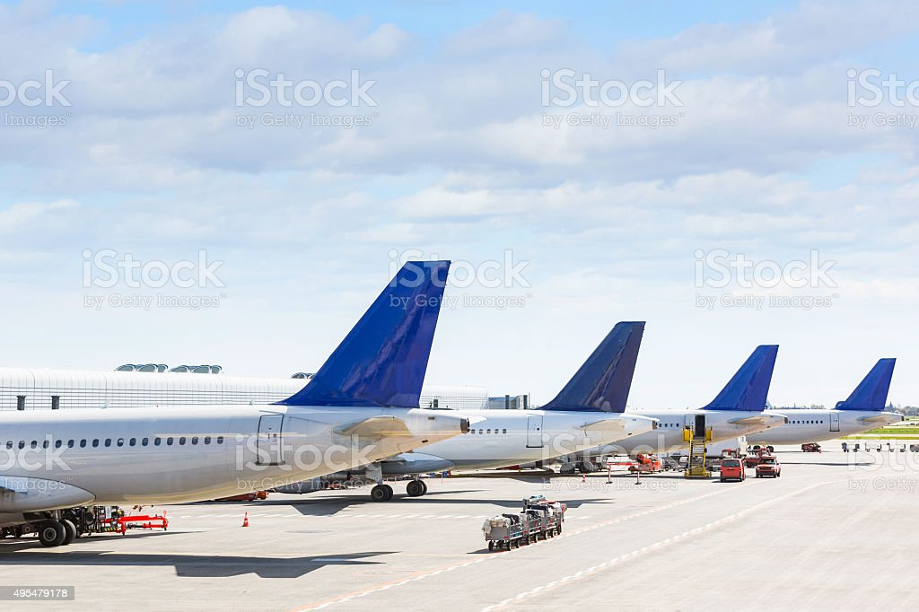 Tails of some airplanes at airport during boarding operation stock photo