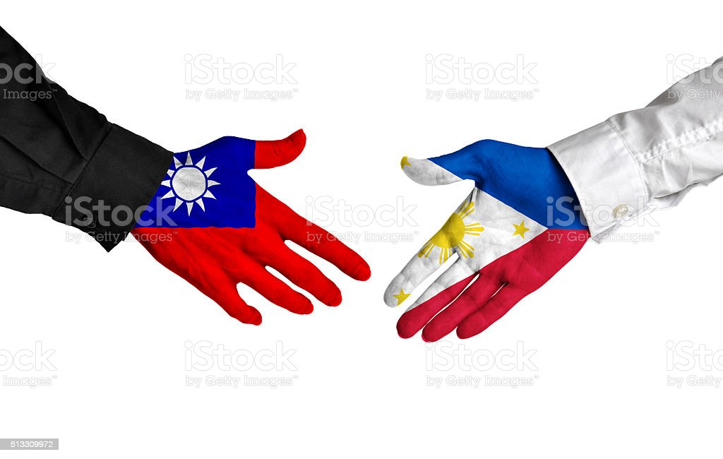 Taiwan and Philippines leaders shaking hands on a deal agreement stock photo