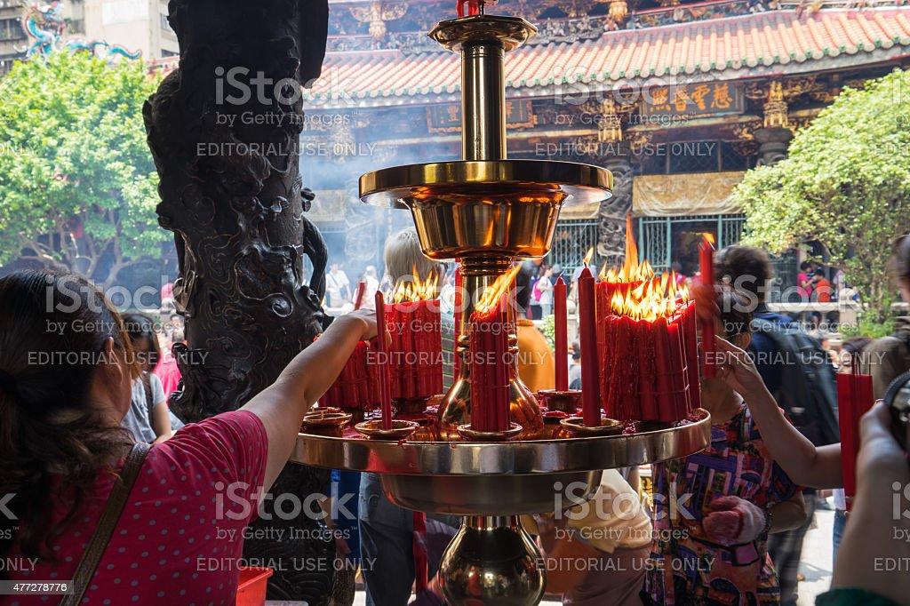 Taiwanese women lighting candles at Longshan Temple stock photo