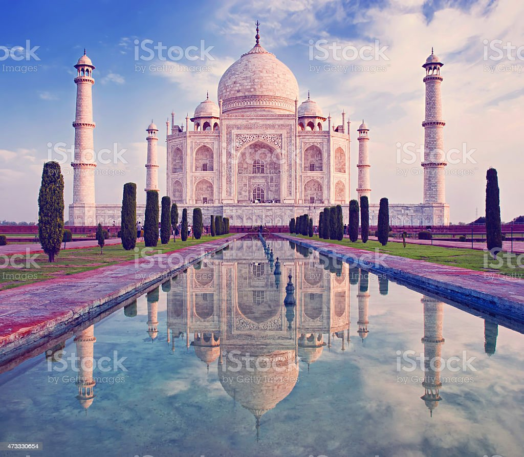 Taj Mahal at sunrise featuring water and sky stock photo