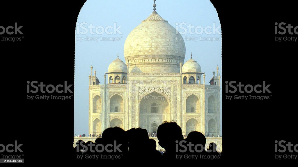 Taj Mahal framed in arch and peoples shadow stock photo