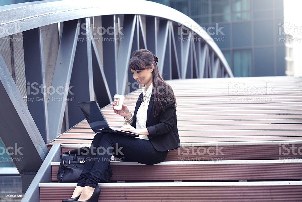 Businesswoman in front of an office building have a break.Drinking...