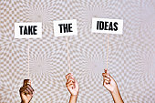 'Take the ideas' say hand-held signs on psychedelic background