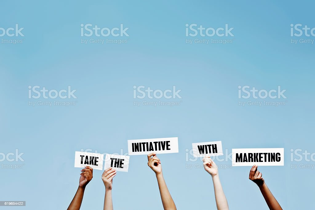 'Take the initiative with Marketing' say hand-held words stock photo