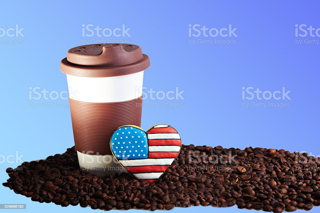Takeaway ceramic cup and coffee beans on blue background stock photo