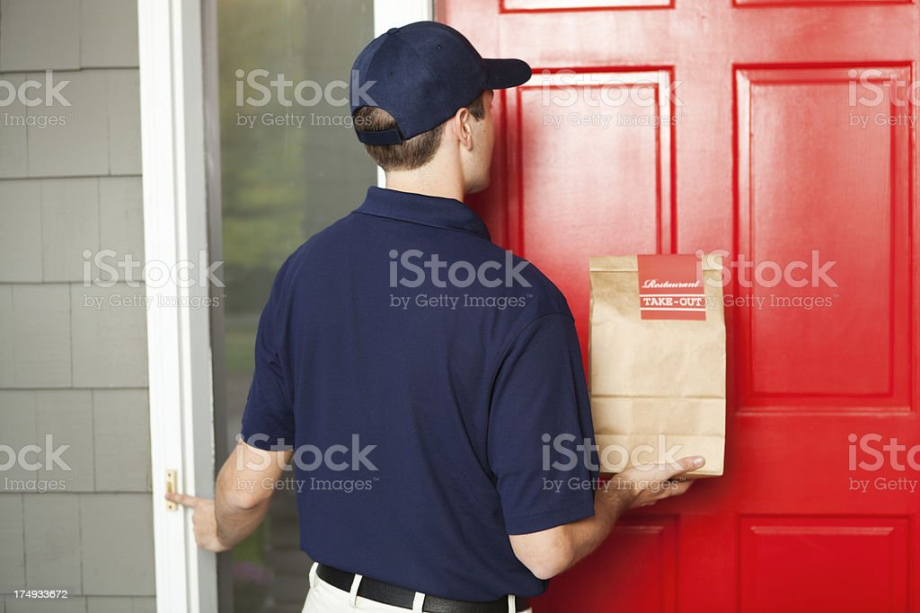A take-out food delivery man delivering take-out food to customer\'s...