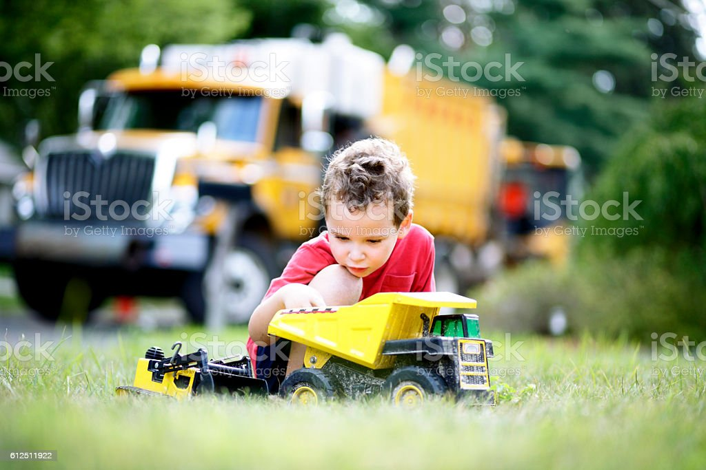 Takes concentration to make believe play with toy trucks stock photo