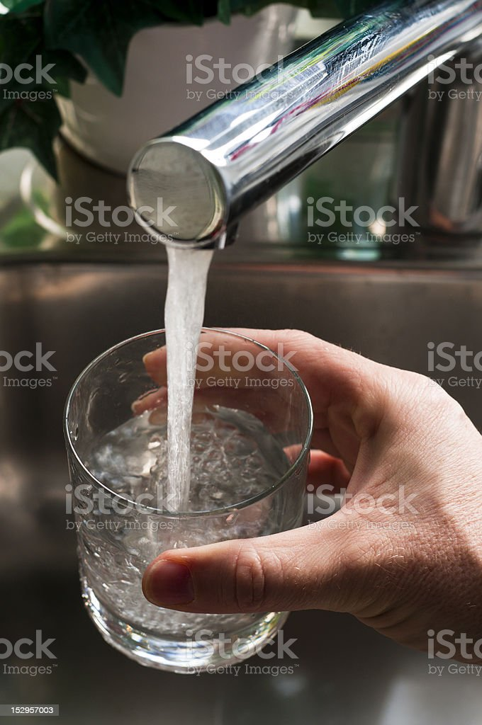 Takiing a glass of water from faucet royalty-free stock photo