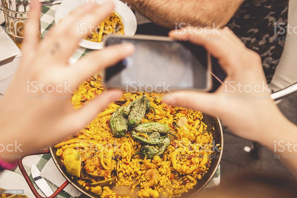 Taking a photo of Spanish paella on smartphone royalty-free stock photo