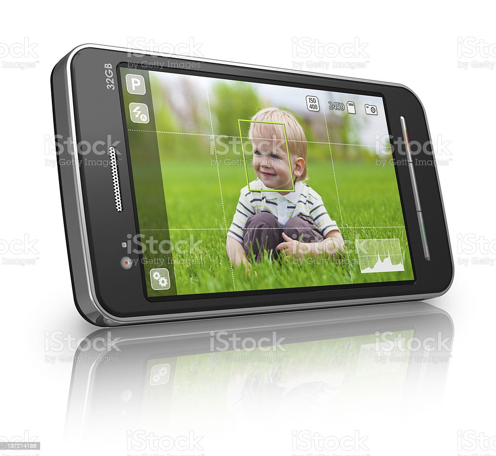 Taking a picture of a boy in a field with a cellphone stock photo