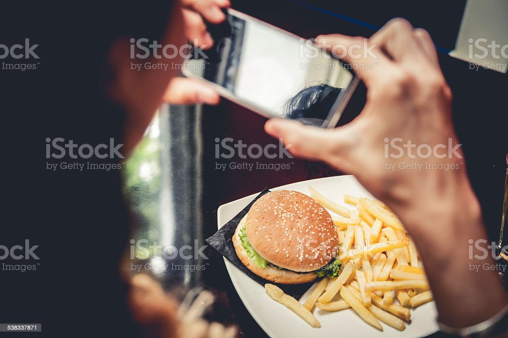 Taking a picture of an hamburger with french fries stock photo