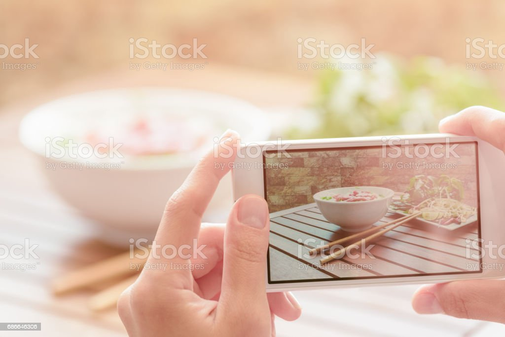 Taking a picture of beef noodle soup in street cafe in Vietnam stock photo