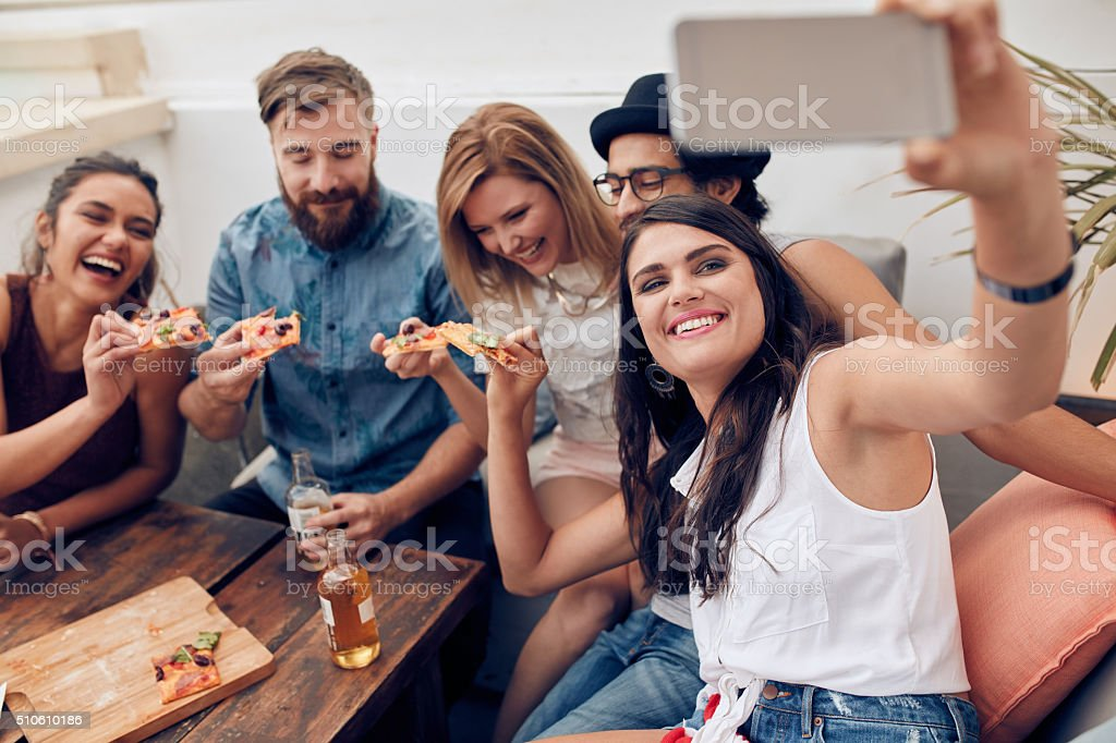 Taking a selfie during a pizza party stock photo