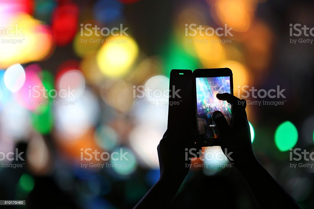 Taking A Smart Phone Photo At An Entertainment Performance stock photo