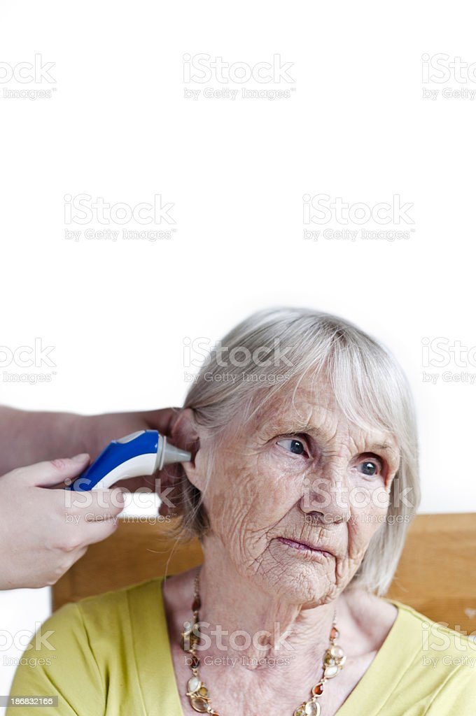 Taking An Elderly Patients Temperature Aurally stock photo